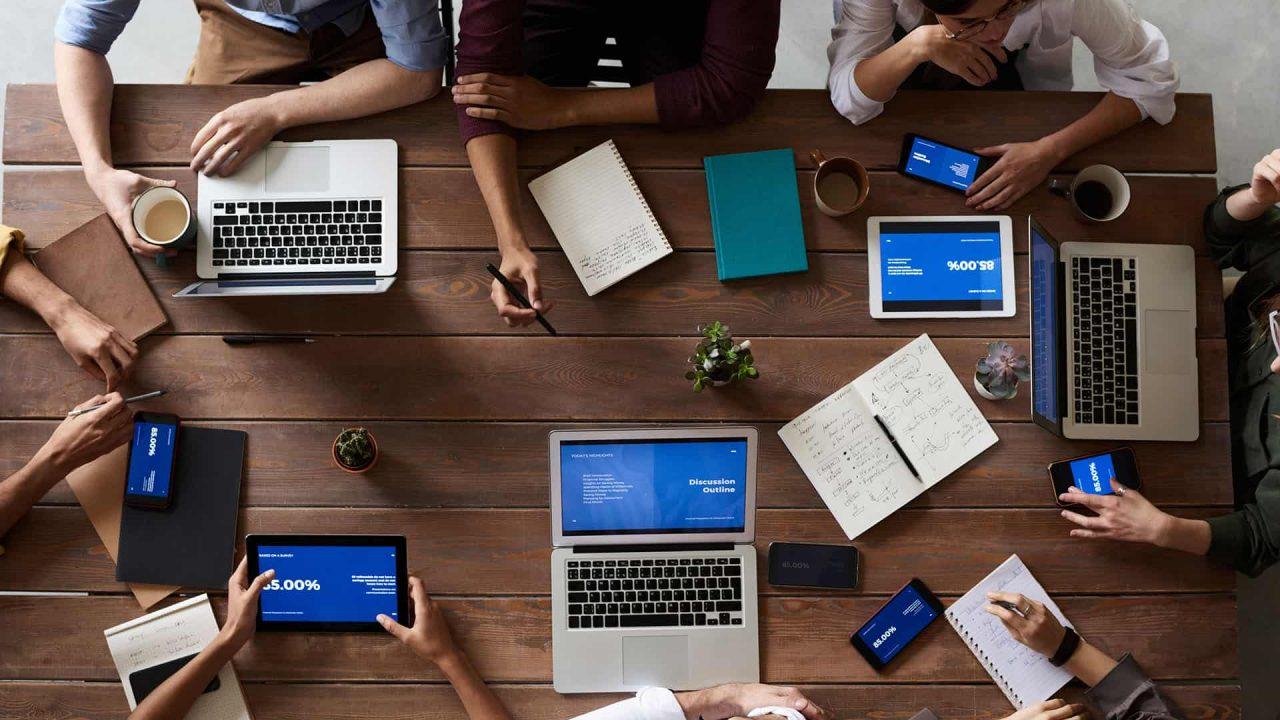 Personas trabajando con notebooks y tablets sobre un escritorio