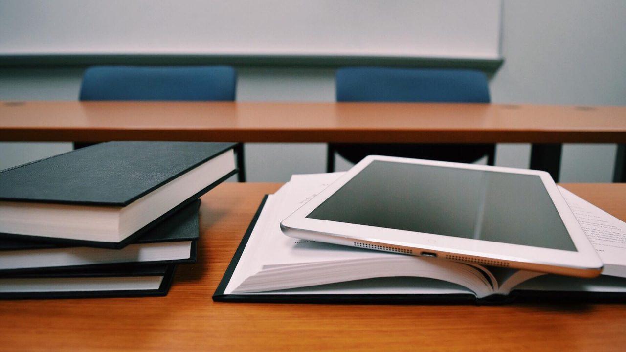 Una pila de tres libros cerrados a la izquierda y un libro abierto donde apoya una tablet