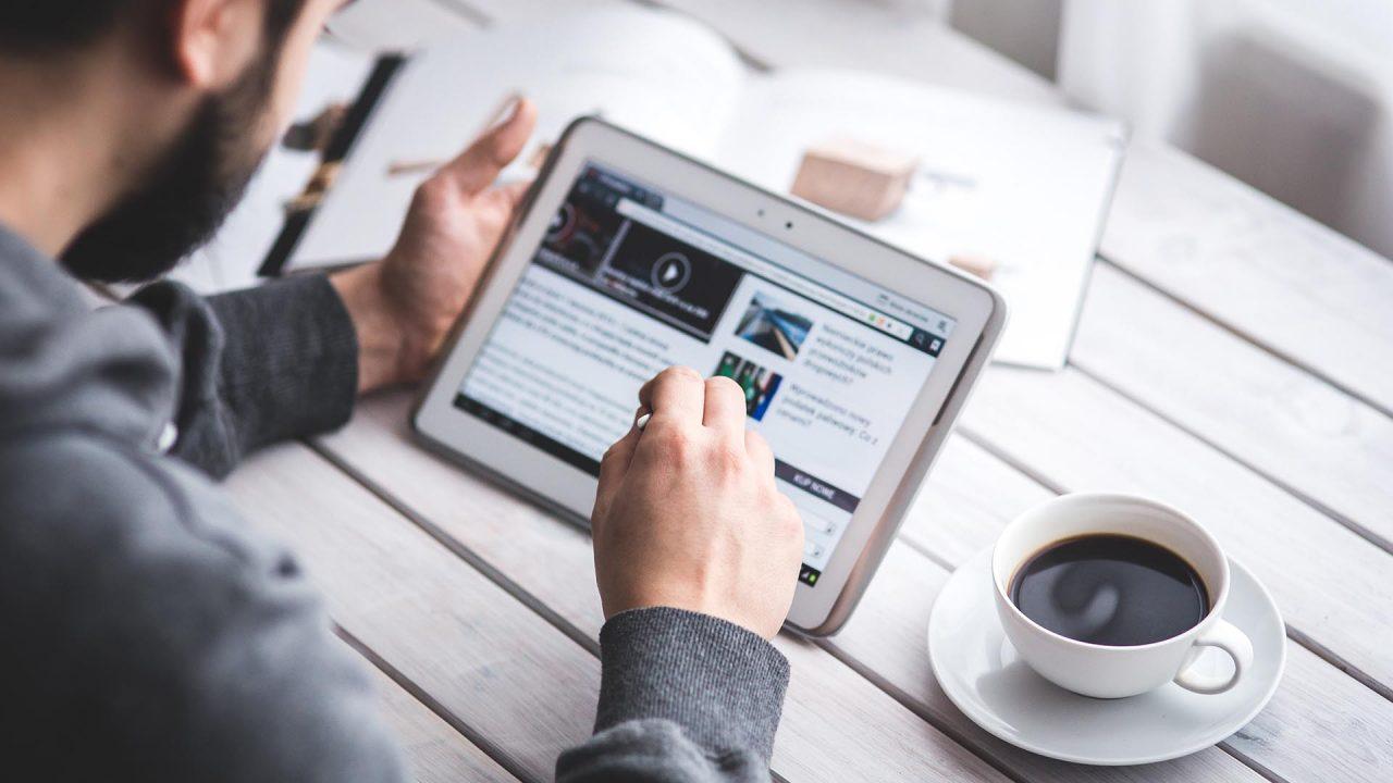 Una persona trabajando con una tablet con una taza de café a su derecha