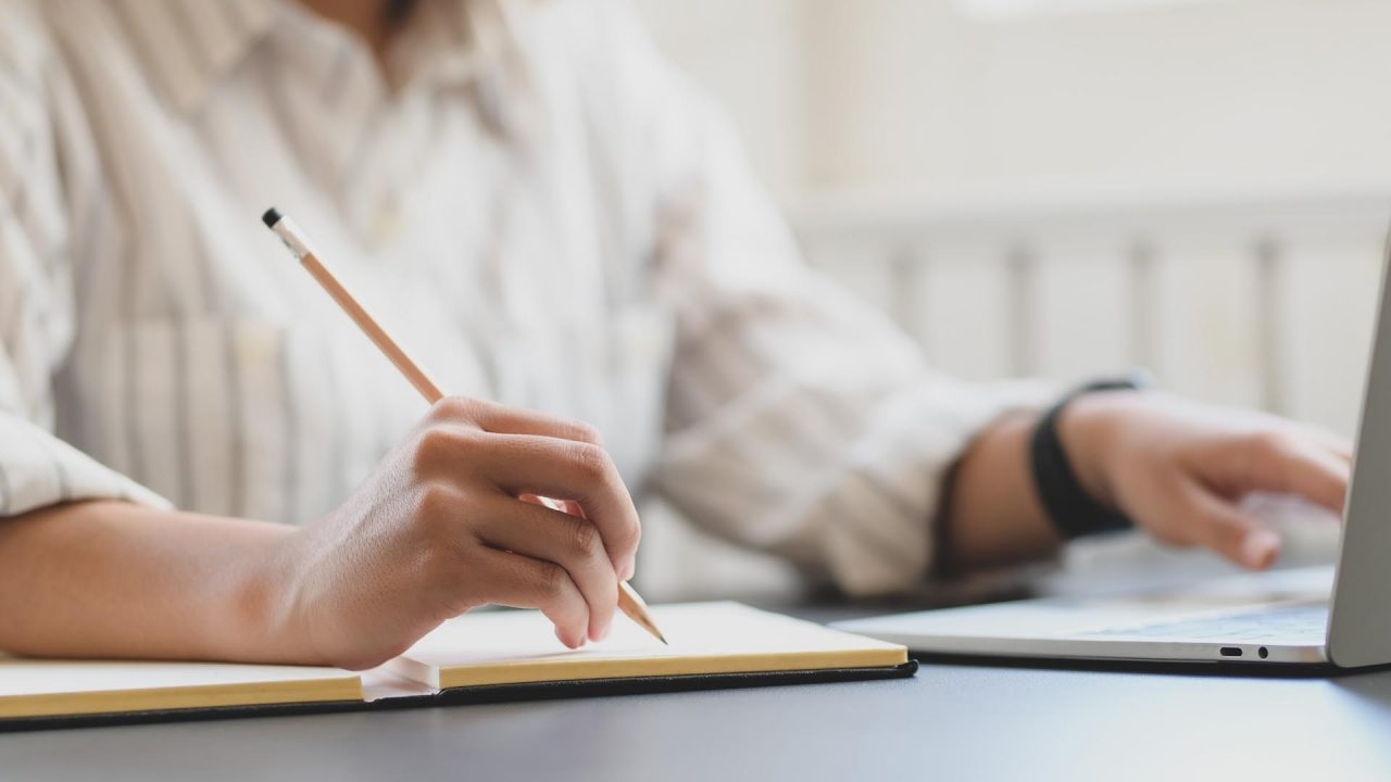 Una mujer tomando notas que lee en una notebook
